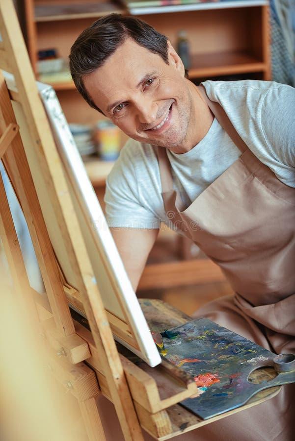 Het gelukkige kunstenaar stellen in het schilderen van studio stock afbeeldingen
