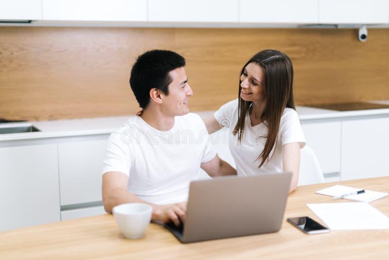 Het gelukkige lachende paar gebruikt samen laptop en bekijkt thuis elkaar royalty-vrije stock afbeelding