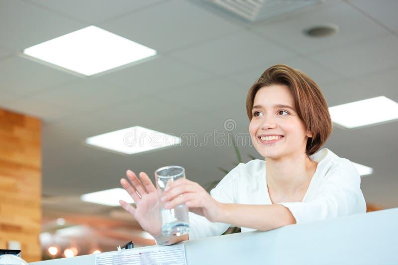 Het gelukkige leuke glas van de vrouwenholding water in bureau royalty-vrije stock foto's