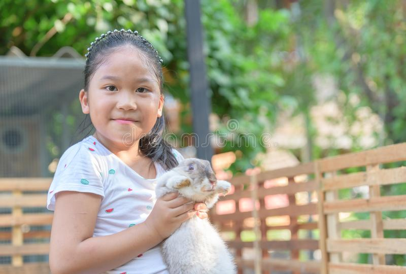 Het gelukkige leuke konijn van de meisjesomhelzing in landbouwbedrijf stock afbeelding