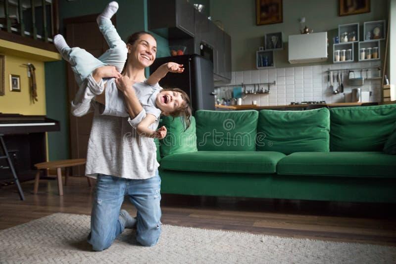 Het gelukkige mamma of babysitter spelen met jong geitjemeisje thuis royalty-vrije stock afbeelding