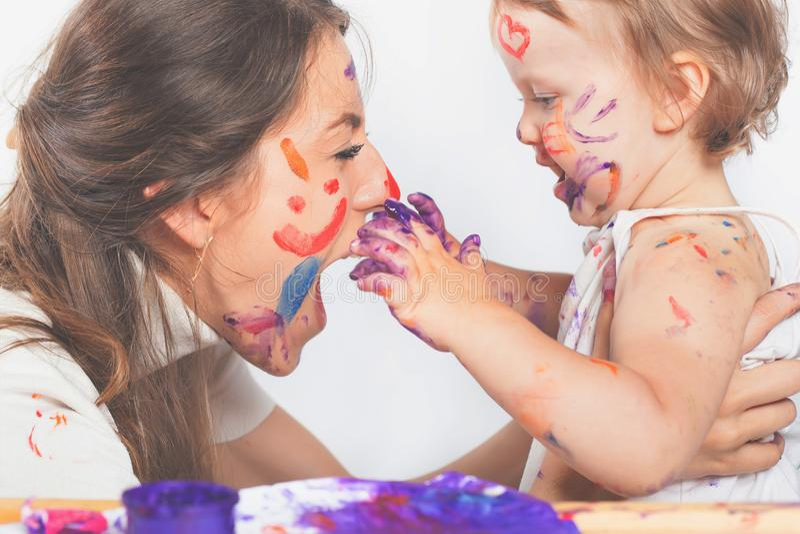 Het gelukkige mamma en baby spelen met geschilderd gezicht door verf royalty-vrije stock foto's