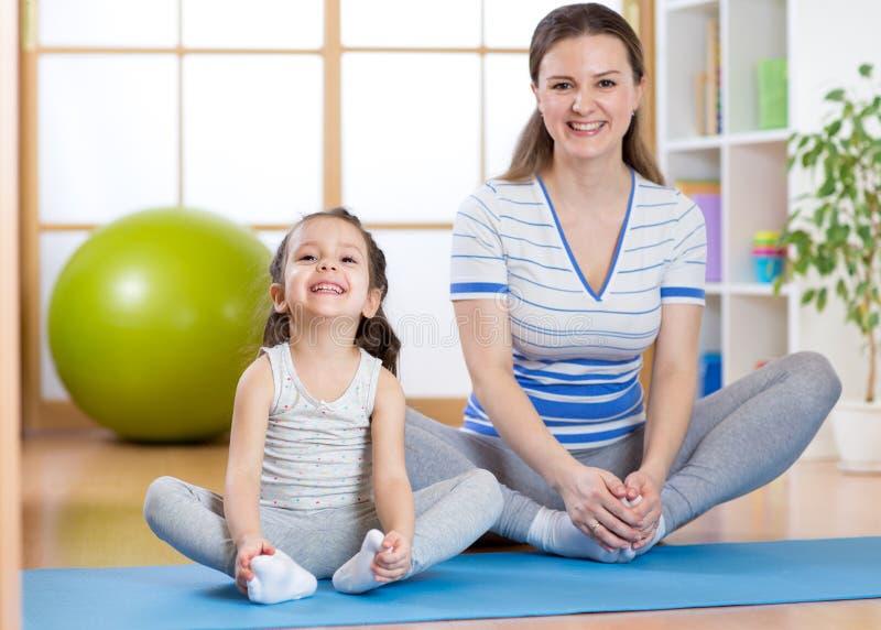 Het gelukkige mamma en het kind brengen tijd in de gymnastiek door stock foto's