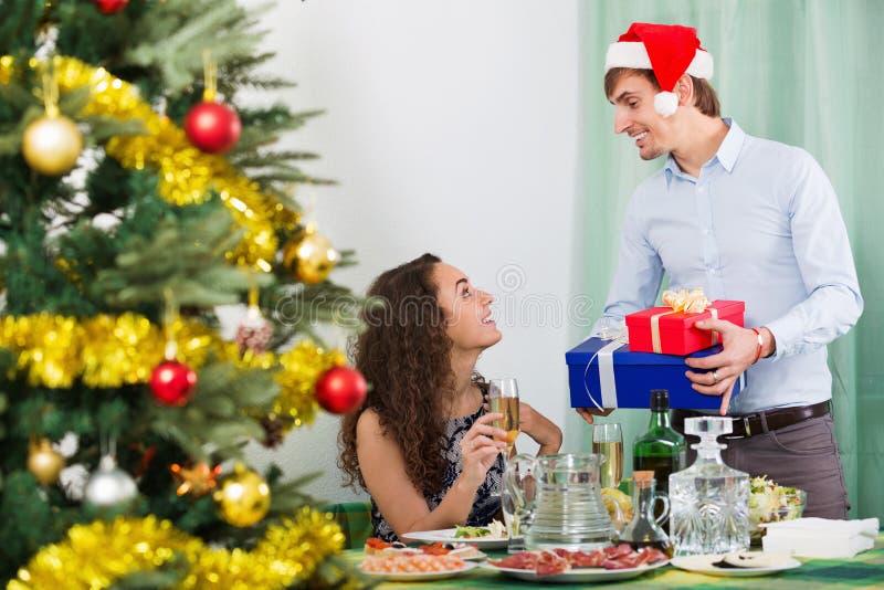 Het gelukkige man aanwezige geven aan vrolijke mooie vrouw stock afbeelding