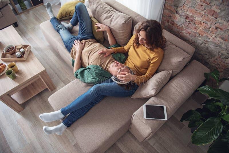 Het gelukkige man en vrouwen ontspannen in woonkamer stock fotografie
