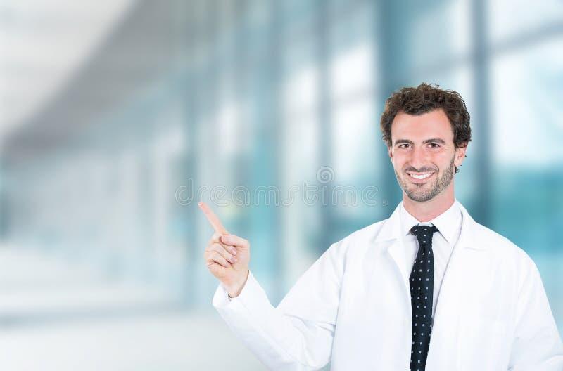 Het gelukkige mannelijke arts glimlachen die met weg omhoog vinger richten royalty-vrije stock afbeelding