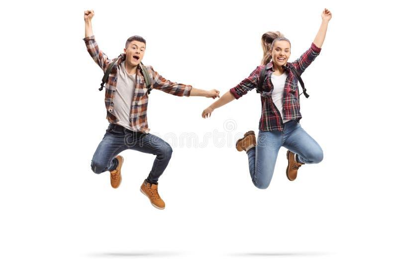 Het gelukkige mannelijke en vrouwelijke studenten springen royalty-vrije stock foto's