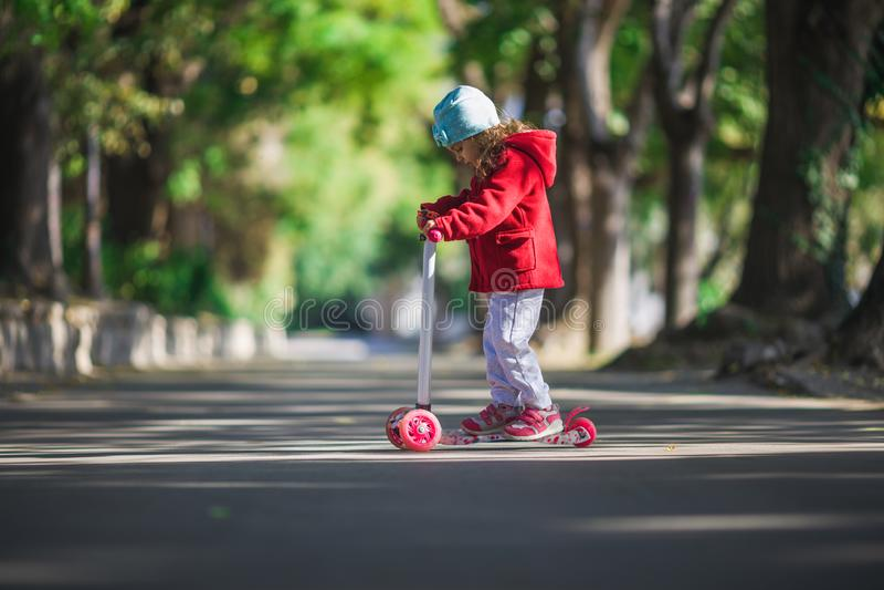Het gelukkige meisje berijdt de autoped in het stedelijke park stock fotografie