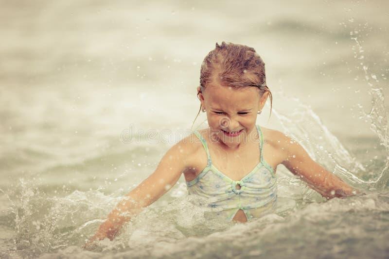 Het gelukkige meisje bespatten in het overzees stock fotografie