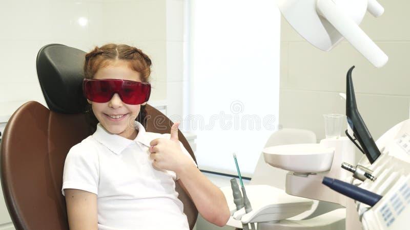 Het gelukkige meisje bij de ontvangst bij de tandarts toont duimen stock afbeelding