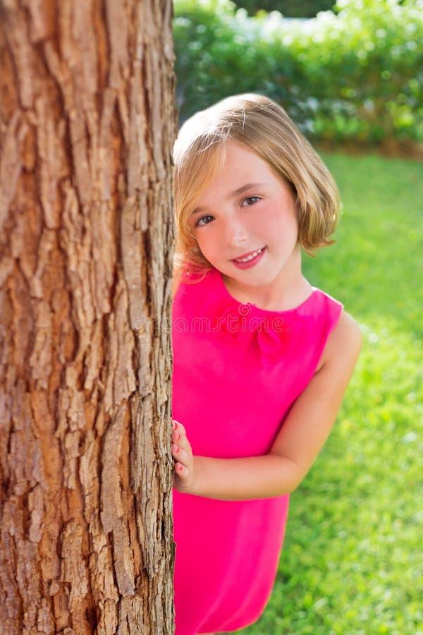 Het gelukkige meisje dat van het kind achterboomboomstam in tuin glimlacht royalty-vrije stock foto's