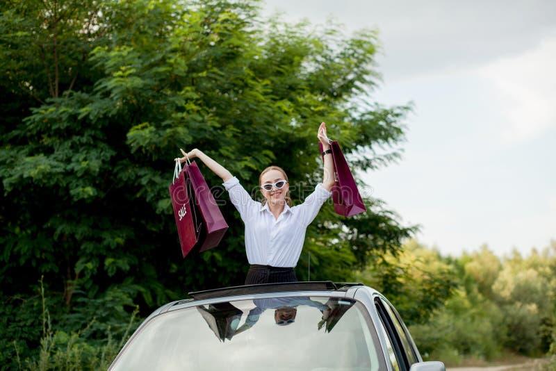 Het gelukkige meisje die de het winkelen pakketten in de auto houden broedt, concept kortingen en het winkelen uit royalty-vrije stock afbeeldingen