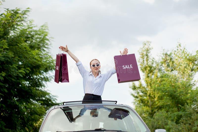 Het gelukkige meisje die de het winkelen pakketten in de auto houden broedt, concept kortingen en het winkelen uit royalty-vrije stock fotografie