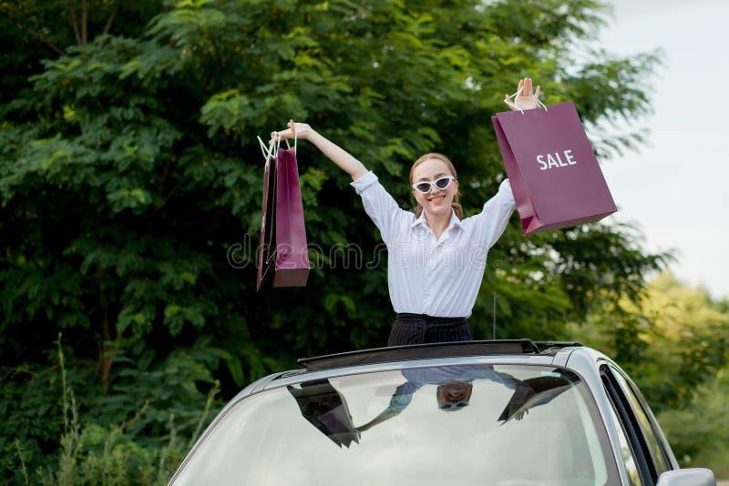 Het gelukkige meisje die de het winkelen pakketten in de auto houden broedt, concept kortingen en het winkelen uit royalty-vrije stock foto