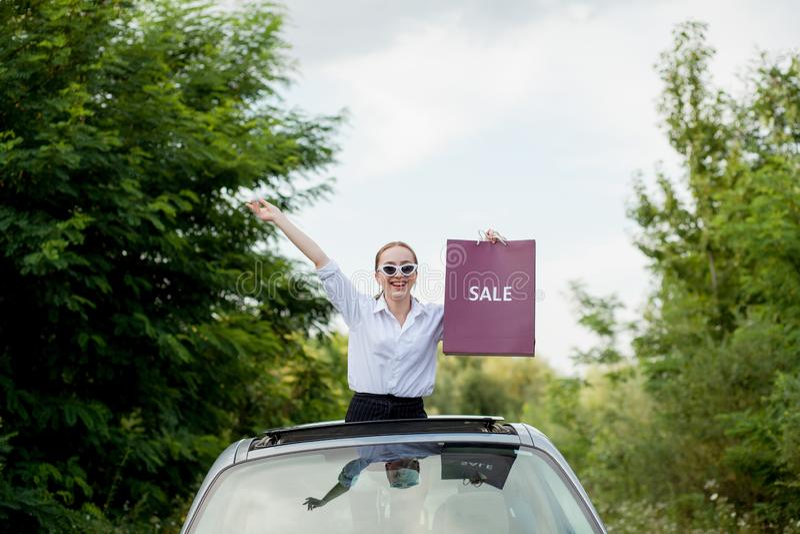 Het gelukkige meisje die de het winkelen pakketten in de auto houden broedt, concept kortingen en het winkelen uit stock foto