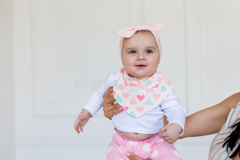 Het gelukkige meisje die van de zuigelingsbaby in de lucht door haar ouder worden gesteund Glimlachende leuke baby 6 maanden oud royalty-vrije stock afbeelding