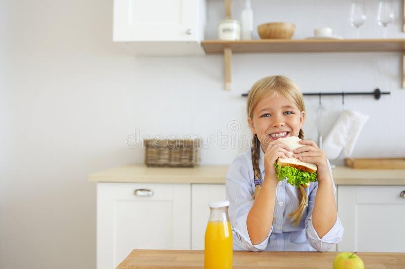 Het gelukkige meisje die van het gezonde ontbijt eten genieten klemt en vruchten en het drinken jus d'orangezitting bij heldere z royalty-vrije stock foto
