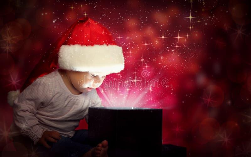 Het gelukkige meisje die van het babykind in Kerstmishoed een magische giftdoos openen stock afbeelding