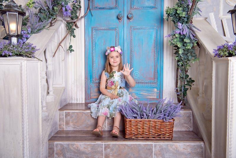 Het gelukkige meisje in een de zomer kleurrijke kleding zit op de portiek stock foto
