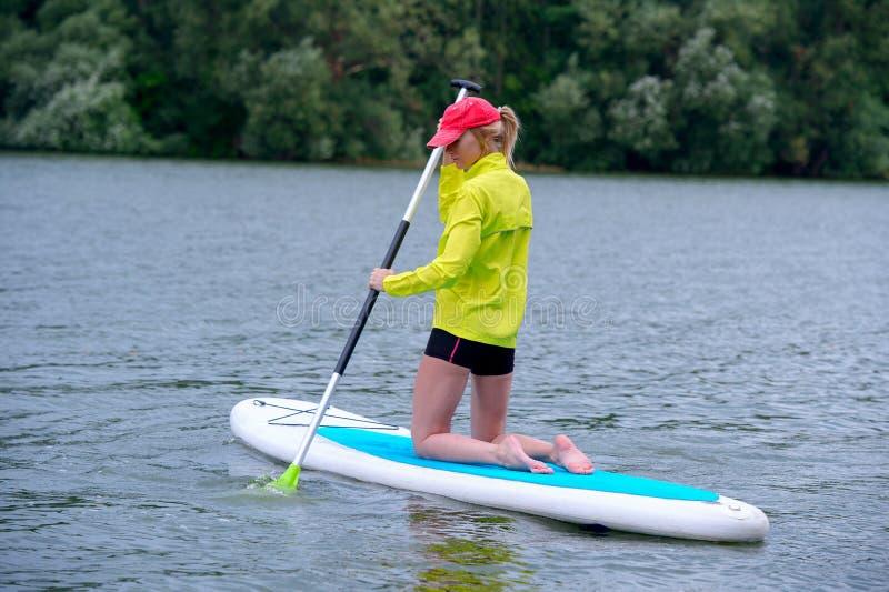 Het gelukkige meisje in een jasje knielt op een surfplank en houdt een lange peddel Achtermeningsfoto royalty-vrije stock fotografie