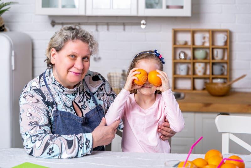Het gelukkige meisje en haar grootmoeder hebben samen ontbijt in een witte keuken Zij hebben pret en spelen met vruchten stock afbeeldingen
