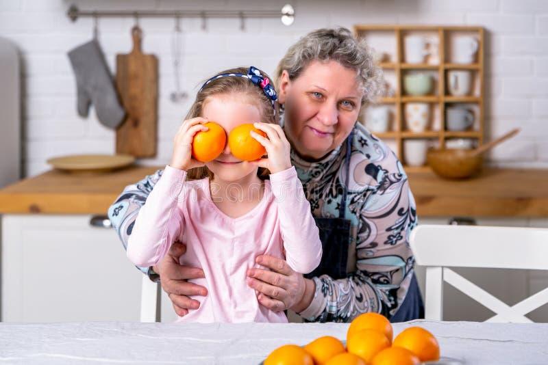 Het gelukkige meisje en haar grootmoeder hebben samen ontbijt in een witte keuken Zij hebben pret en spelen met vruchten royalty-vrije stock afbeelding