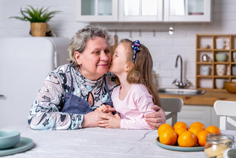 Het gelukkige meisje en haar grootmoeder hebben samen ontbijt in een witte keuken Zij hebben pret en spelen met vruchten royalty-vrije stock foto's