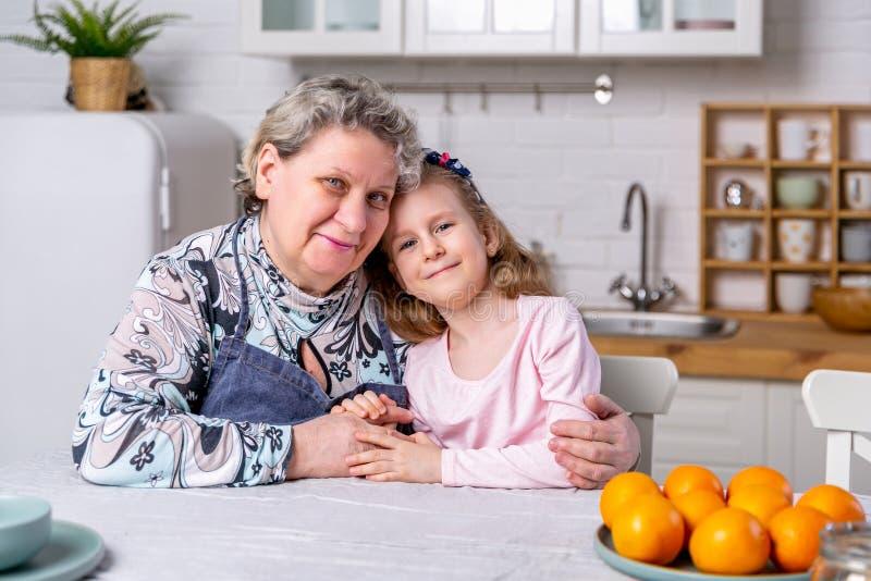 Het gelukkige meisje en haar grootmoeder hebben samen ontbijt in een witte keuken Zij hebben pret en spelen met vruchten royalty-vrije stock afbeeldingen