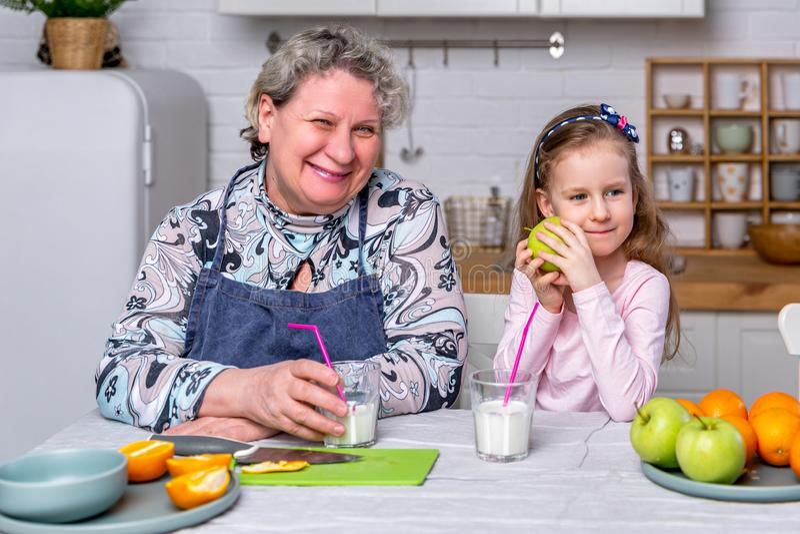 Het gelukkige meisje en haar grootmoeder hebben samen ontbijt in een witte keuken Zij hebben pret en spelen met vruchten royalty-vrije stock fotografie