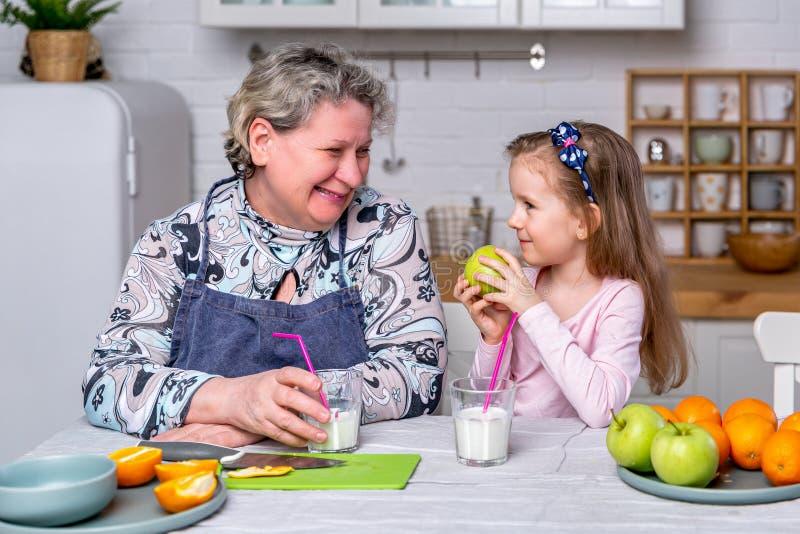 Het gelukkige meisje en haar grootmoeder hebben samen ontbijt in een witte keuken Zij hebben pret en spelen met vruchten stock afbeelding