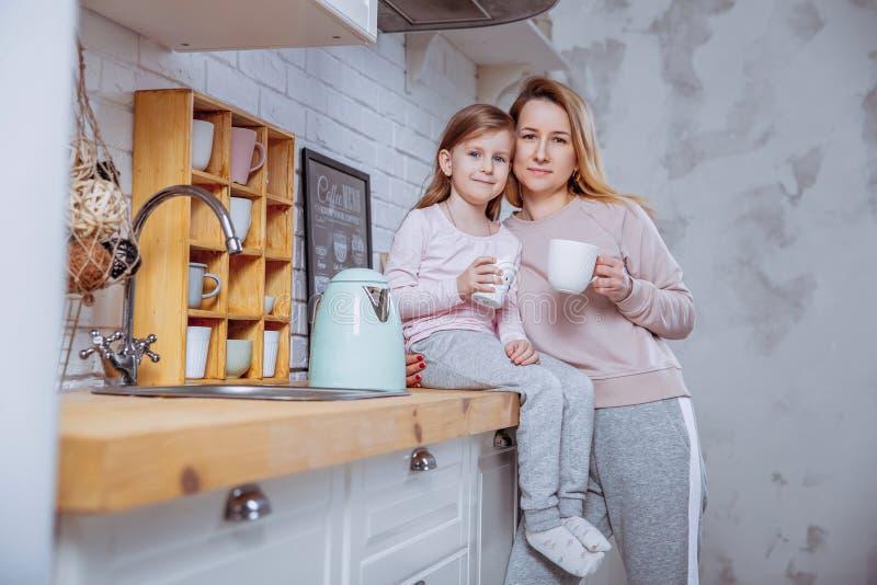 Het gelukkige meisje en haar mooie jonge moeder hebben samen ontbijt in een witte keuken Zij koesteren en drinken thee Moeder Zor royalty-vrije stock fotografie