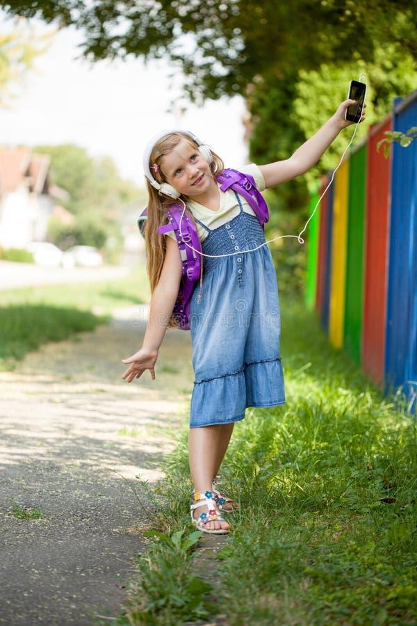 Het gelukkige meisje gaat naar school en luistert aan muziek via smartph royalty-vrije stock fotografie