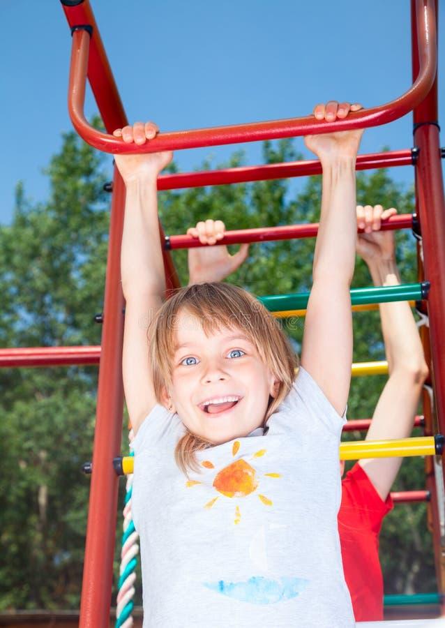Het gelukkige meisje hangen van een wildernisgymnastiek in een de zomertuin royalty-vrije stock foto's