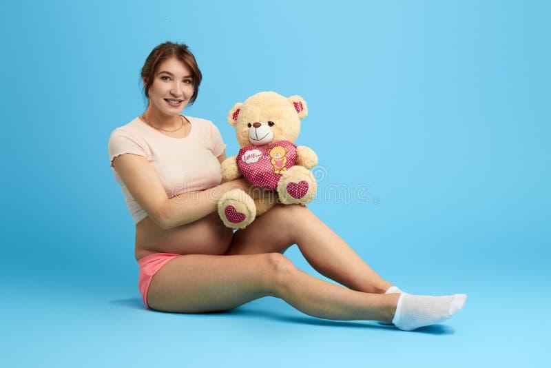 Het gelukkige meisje heeft vuiststuk speelgoed voor haar baby voorbereid stock fotografie