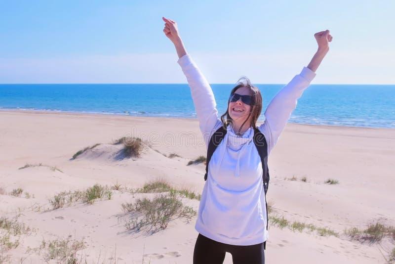 Het gelukkige meisje heft omhoog haar wapens op het concept van de het strandwinnaar van het kustzand op vakantie op stock foto's
