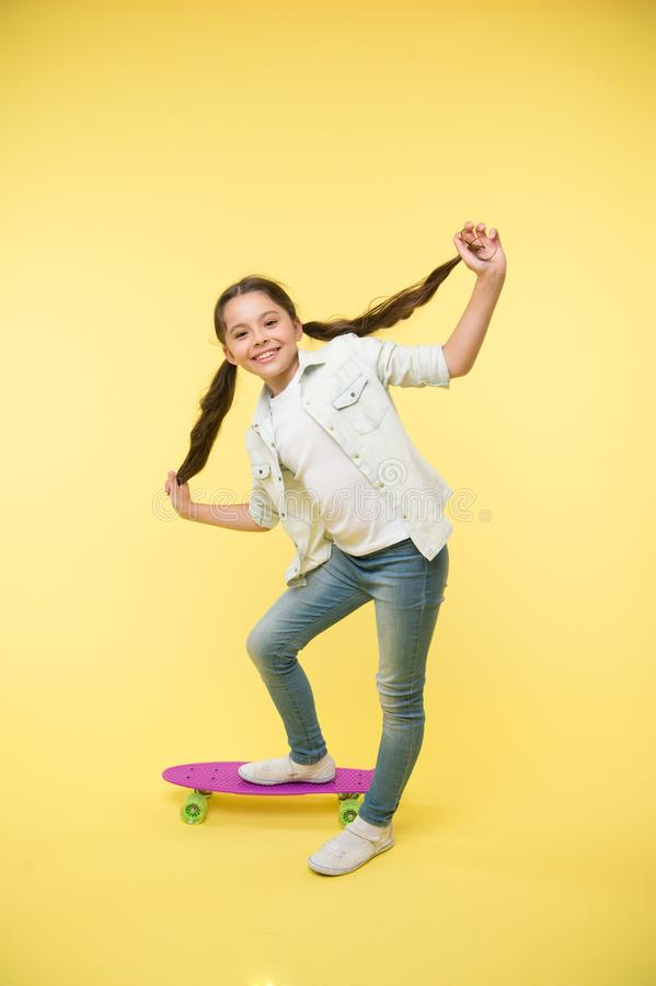 Het gelukkige meisje hipster toont lang donkerbruin haar op stuiverraad op gele achtergrond Weinig kindglimlach met nieuw kapsel stock afbeelding