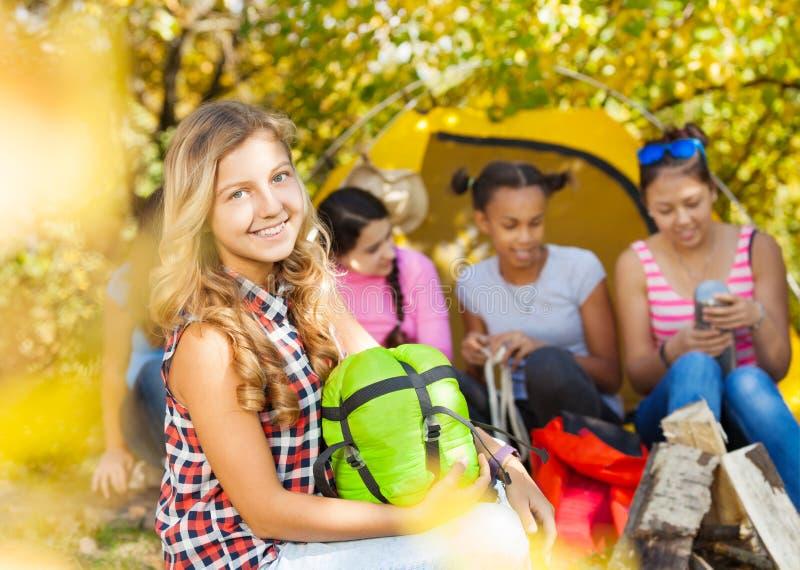 Het gelukkige meisje houdt groene slaapzak tijdens het kamperen royalty-vrije stock fotografie