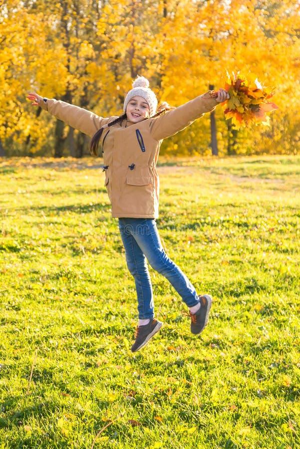 Het gelukkige meisje kleedde zich in een hoed en warme jasjedansen die op de gevallen esdoornbladeren springen in verticaal de he stock afbeelding
