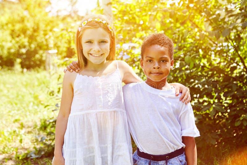 Het gelukkige meisje koestert Afrikaans adoptiekind stock fotografie