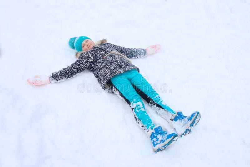 Het gelukkige meisje ligt op sneeuw en speelt Engel stock foto