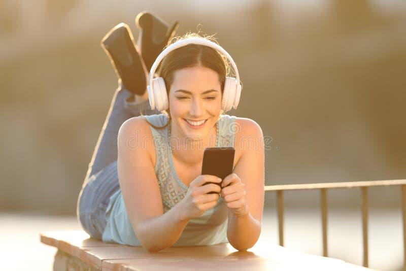 Het gelukkige meisje luistert aan muziek het doorbladeren telefooninhoud stock fotografie