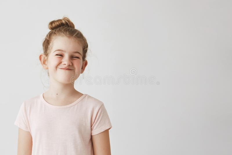 Het gelukkige meisje met blond lang haar in broodjeskapsel het grappige glimlachen met losed ogen, makend dwaze gezichten op scho royalty-vrije stock afbeelding