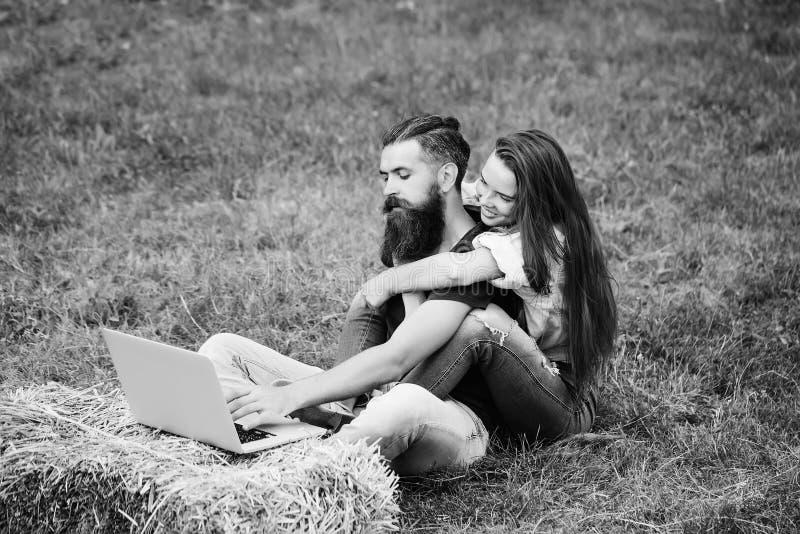 Het gelukkige meisje omhelst de gebaarde mens hipster werkend aan laptop stock afbeeldingen