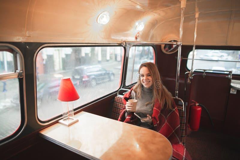 Het gelukkige meisje is omvat met een algemene zitting in een koffie met een origineel retro binnenland royalty-vrije stock afbeeldingen