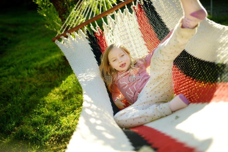 Het gelukkige meisje ontspannen in hangmat op mooie de zomerdag Leuk kind die pret in de lentetuin hebben royalty-vrije stock fotografie