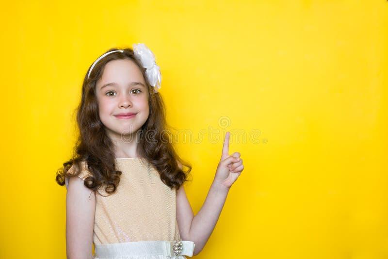 Het gelukkige meisje op gele achtergrond richt haar vinger op de ruimte voor het van letters voorzien Concept onderwijs stock foto