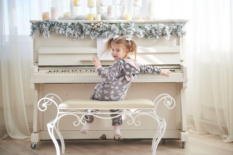 Het gelukkige meisje speelt de piano op Kerstmisdag stock afbeelding