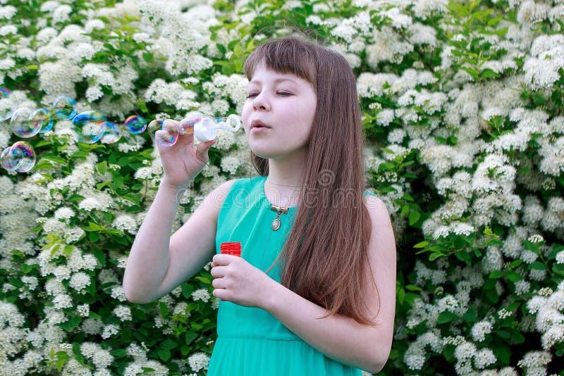 Het gelukkige meisje speelt met zeepbels stock afbeelding