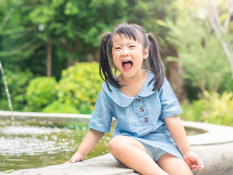 Het gelukkige meisje spelen bij de fontein op bokehachtergrond H stock afbeelding