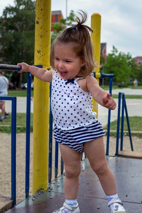 Het gelukkige meisje spelen bij speelplaats royalty-vrije stock afbeelding